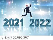Businessman jumping from year 2021 to 2022. Стоковое фото, фотограф Elnur / Фотобанк Лори