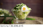 Spring salad with early cabbage, cucumbers, eggs and green onions. Стоковое видео, видеограф Peredniankina / Фотобанк Лори