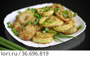 Fried zucchini in circles with fresh herbs in a plate on a black. Стоковое видео, видеограф Peredniankina / Фотобанк Лори