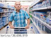 old age man choosing bottle of drinking water in supermarket. Стоковое фото, фотограф Татьяна Яцевич / Фотобанк Лори