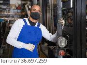 Worker in protective mask standing near forklift in warehouse. Стоковое фото, фотограф Яков Филимонов / Фотобанк Лори