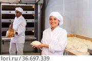 Woman baker smiling at camera during daily work with dough. Стоковое фото, фотограф Яков Филимонов / Фотобанк Лори