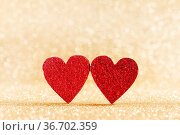 Two small handmade red glitter hearts on bright golden lights bokeh... Стоковое фото, фотограф Zoonar.com/Ivan Mikhaylov / easy Fotostock / Фотобанк Лори