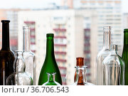 Various empty bottles and view of apartment houses through home window... Стоковое фото, фотограф Zoonar.com/Valery Voennyy / easy Fotostock / Фотобанк Лори
