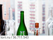 Many empty bottles and view of apartment buildings through home window... Стоковое фото, фотограф Zoonar.com/Valery Voennyy / easy Fotostock / Фотобанк Лори