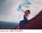 Beautiful woman in long dress sitting with blue colored smoke on tiled... Стоковое фото, фотограф Zoonar.com/Piotr Stryjewski / easy Fotostock / Фотобанк Лори