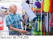mature senor choosing mop in supermarket. Стоковое фото, фотограф Татьяна Яцевич / Фотобанк Лори