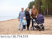 Family with multiple children standing on sandy beach together. Стоковое фото, фотограф Кекяляйнен Андрей / Фотобанк Лори