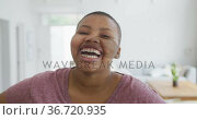 Portrait of smiling african american plus size woman looking at camera and laughing in living room. Стоковое видео, агентство Wavebreak Media / Фотобанк Лори