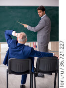 Young male employee and old boss in front of blackboard. Стоковое фото, фотограф Elnur / Фотобанк Лори