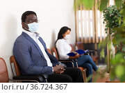 Man in protective mask sits on chair while waiting for reception in company office. Стоковое фото, фотограф Яков Филимонов / Фотобанк Лори