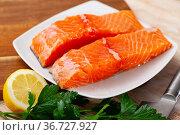 Raw salmon fillet with lemon and greens before cooking. Стоковое фото, фотограф Яков Филимонов / Фотобанк Лори
