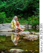 Attractive blonde woman on a Green forest river with flowers in hand... Стоковое фото, фотограф Emil Pozar / age Fotostock / Фотобанк Лори