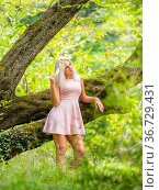 Attractive blonde woman daydreaming next to a big tree in forest. Стоковое фото, фотограф Emil Pozar / age Fotostock / Фотобанк Лори