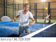 Male player ready to hits the ball while playing padel. Стоковое фото, фотограф Яков Филимонов / Фотобанк Лори