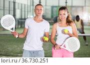 Couple with padel rackets posing on tennis court. Стоковое фото, фотограф Яков Филимонов / Фотобанк Лори