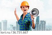 Expressive woman in safety helmet shouting into megaphone. Portrait... Стоковое фото, фотограф Zoonar.com/Aleksandr Khakimullin / easy Fotostock / Фотобанк Лори