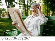 An elderly woman reading newspaper on the bench. Стоковое фото, фотограф Tryapitsyn Sergiy / Фотобанк Лори