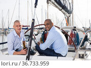 Two men in blue shirts relaxing on sailing yacht in the port. Стоковое фото, фотограф Татьяна Яцевич / Фотобанк Лори