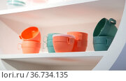 Various plastic new empty reusable mugs. Cookware in trendy pastel colors. Industrial background, kitchen interior. Стоковое фото, фотограф Светлана Евграфова / Фотобанк Лори