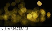 Multiple yellow fairy lights glowing on black background. Стоковое фото, агентство Wavebreak Media / Фотобанк Лори