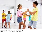 Tween boy and girl practicing dynamic boogie-woogie in pair during group class. Стоковое фото, фотограф Яков Филимонов / Фотобанк Лори
