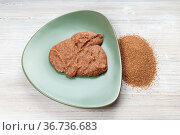 Teff grains and boiled porridge on green plate on wooden table. Стоковое фото, фотограф Zoonar.com/Valery Voennyy / easy Fotostock / Фотобанк Лори