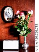 Wall clock, blank calendar and pink roses in pewter jug on dark brown... Стоковое фото, фотограф Zoonar.com/Valery Voennyy / easy Fotostock / Фотобанк Лори