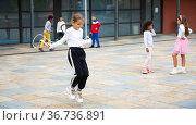 Sporty tween girl jumping rope in school yard during recess. Стоковое фото, фотограф Яков Филимонов / Фотобанк Лори