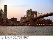 Brooklyn Bridge (1883), hybrid cable-stayed suspension bridge, at sunset in New York City. United States. Стоковое фото, фотограф Валерия Попова / Фотобанк Лори