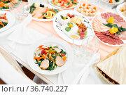 Fresh salads on holiday table. Wine glasses with napkins, glasses... Стоковое фото, фотограф Zoonar.com/Konstantin Malkov / easy Fotostock / Фотобанк Лори