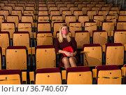 Reflective woman in protective mask sitting alone in empty cinema house. Стоковое фото, фотограф Яков Филимонов / Фотобанк Лори