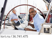 man working at the laptop and drinking coffee on private yachts in the seaport. Стоковое фото, фотограф Татьяна Яцевич / Фотобанк Лори