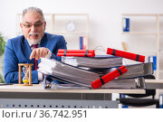 Old male employee with dynamite in the office. Стоковое фото, фотограф Elnur / Фотобанк Лори