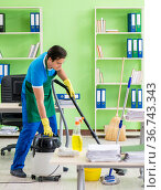 Handsome man cleaning office with vacuum cleaner. Стоковое фото, фотограф Elnur / Фотобанк Лори