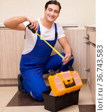 Young repairman working at the kitchen. Стоковое фото, фотограф Elnur / Фотобанк Лори
