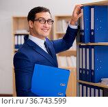Handsome businessman standing next to shelf. Стоковое фото, фотограф Elnur / Фотобанк Лори