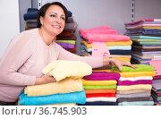 woman shopper chooses multi colored terry towels in store. Стоковое фото, фотограф Татьяна Яцевич / Фотобанк Лори
