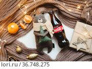 Christmas mood concept. Cozy composition with plaid, toy bear, coca cola, tangerines and traditional festive decorations. Belarus, Minsk, 15.10.21. Редакционное фото, фотограф Galina kondratenko / Фотобанк Лори