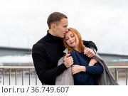 Couple in love, guy puts his jacket on girl's shoulders in cold weather. Стоковое фото, фотограф Евгений Харитонов / Фотобанк Лори