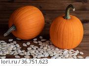 Pumpkins and seeds on wooden backdrop. Стоковое фото, фотограф Иван Михайлов / Фотобанк Лори