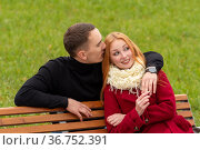 Romantic young couple on a park bench, the guy whispers in the girl ear. Стоковое фото, фотограф Евгений Харитонов / Фотобанк Лори