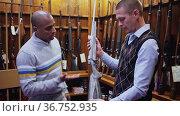 Latin american man owner of gun shop consulting customer about modern sporting rifle before purchase. Стоковое видео, видеограф Яков Филимонов / Фотобанк Лори