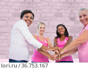 Portrait of group of women stacking their hands together against brick wall in background. Стоковое фото, агентство Wavebreak Media / Фотобанк Лори