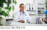 Focused physician filling up medical forms on laptop in office. Стоковое фото, фотограф Яков Филимонов / Фотобанк Лори