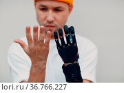 Young disabled man checking and looking on artificial prosthetic hand... Стоковое фото, фотограф Zoonar.com/Max / easy Fotostock / Фотобанк Лори