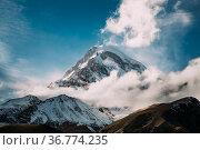 Stepantsminda, Gergeti, Georgia. Peak Of Mount Kazbek Covered With... Стоковое фото, фотограф Ryhor Bruyeu / easy Fotostock / Фотобанк Лори