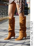 Sexy female legs in high leather boots and short dress. Fashion and... Стоковое фото, фотограф Aleksandar Ilic / easy Fotostock / Фотобанк Лори