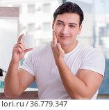 Young handsome man applying face cream. Стоковое фото, фотограф Elnur / Фотобанк Лори