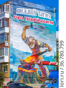 Russia, Nizhny Tagil, July 2021: a landmark of the city 15 meter reproduction of the painting The Gray Ural forges a victory on a five-story house on a sunny summer day. Text in Russian: Nizhny Tagil city of labor valor. Редакционное фото, фотограф Акиньшин Владимир / Фотобанк Лори